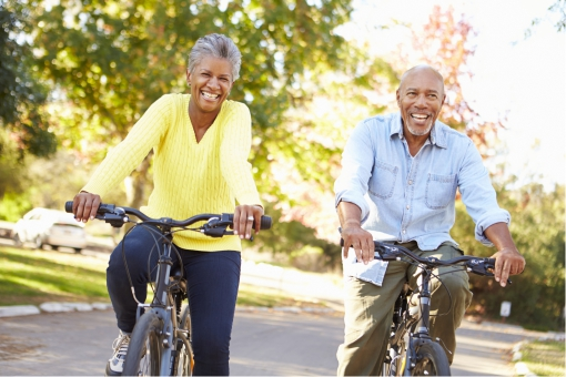 Mature couple riding bicycles smiling